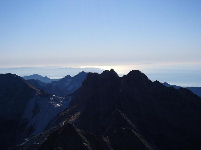 Dalla vetta del Pisanino la dentellata cresta del M.Cavallo. Dietro il mare e l'Isola d'Elba